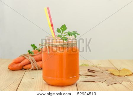 Carrot smoothie in a glass jar and vegetables on a wooden background. Healthy eating concept.