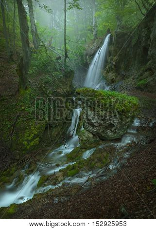 Hidden waterfalls in woods at fogy morning. Travel destination Sopotnica Serbia.
