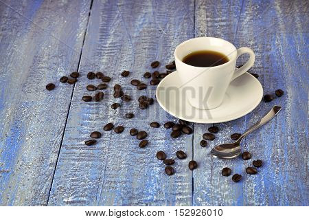 A cup of hot coffee and coffee beans on the old wooden background. Morning. Christmas atmosphere. Celebration. Break. Relax. Recreation.
