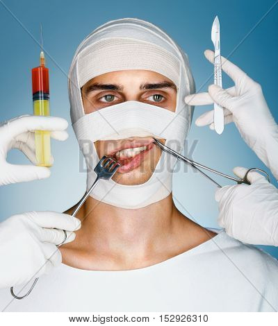 Victim of plastic surgery. Man wrapped in medical bandages while doctors with syringes surgical clamp hook and scalpels near his face. Beauty concept