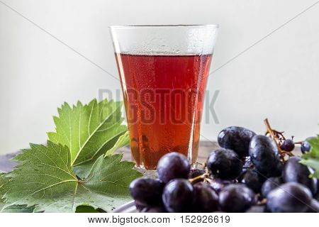 Grape juice and a cluster of grapes with green leaves. Healthy eating.