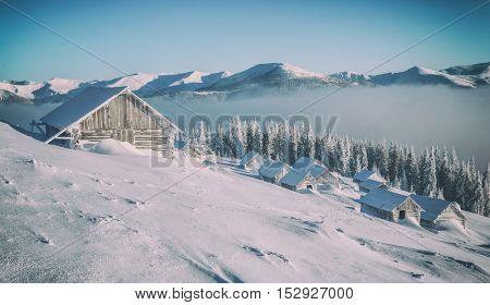 Fantastic landscape glowing by sunlight. Dramatic wintry scene with snowy house. Carpathians, Ukraine, Europe. Toned like Instagram filter