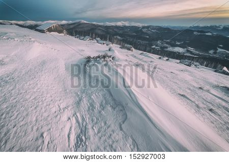 Fantastic pink evening landscape glowing by sunlight. Dramatic wintry scene with snowy house. Carpathians, Ukraine, Europe. Toned like Instagram filter