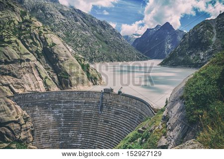 Great view from the top of the Grimsel pass over the Grimselsee dam. Switzerland, Bernese Alps, Europe, toned like Instagram filter