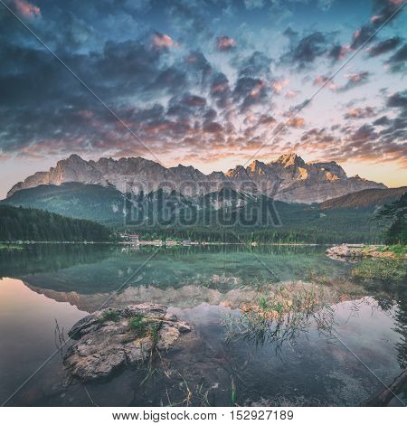 Fantastic sundown on mountain lake Eibsee, located in the Bavaria, Germany. Dramatic unusual scene. Alps, Europe. Toned like Instagram filter