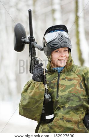 happy female paintball player with marker at winter outdoors