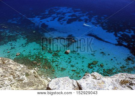 Wonderful view from above from the rock on the sea with amazing colors sea floor and white boats.