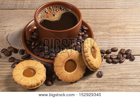 Cup of hot coffee with delicious biscuit on wooden background