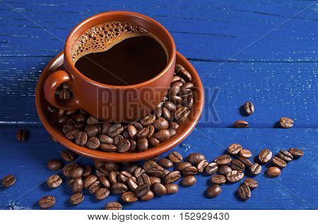 Cup of hot coffee and beans on blue wooden background