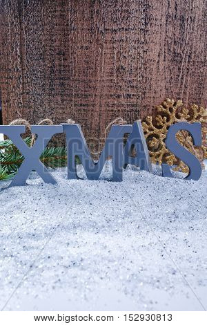 Xmas wooden letters and snowflake on shiny mirrored background
