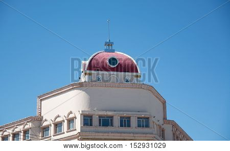 Top of cathedral with white walls and red dome against blue sky as background