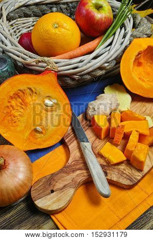 Fresh ingredients for pumpkin soup with apple orange carrot and onion on wooden background