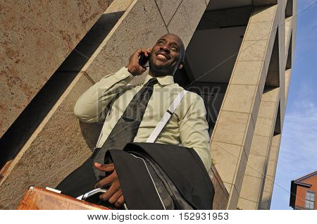 Happy business man speaking on bomile phone outside office building