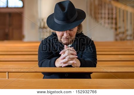 Elderly Lady In Mourning Praying In A Church