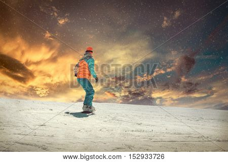 Woman on the snowboard in sport action at sunny day around mountains under blue sky.