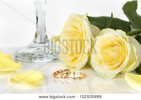 Two gold wedding rings and twu yellow roses