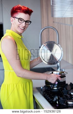 woman in yellow dress standing at stove in kitchen and smiling at camera