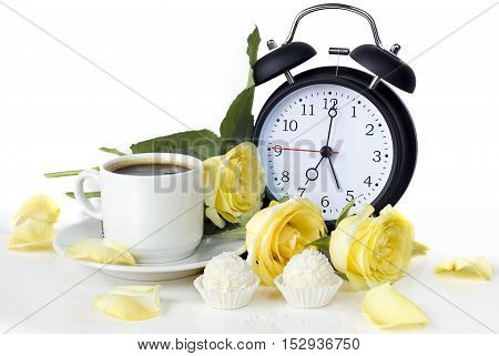 cup of morning coffee sweets with coconut flakes a bouquet of yellow roses and vintage alarm clock on white background