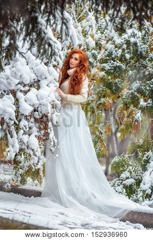 The red-haired young woman in long white dress in the winter wood