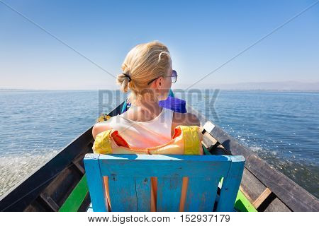 Rear view of female Caucasian tourist traveling by colorful traditional wooden boat on Inle lake, Burma, Myanmar.