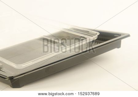 Plastic containers for food. The transparent lid and black bottom. No cover. Horizontal photo. From the side