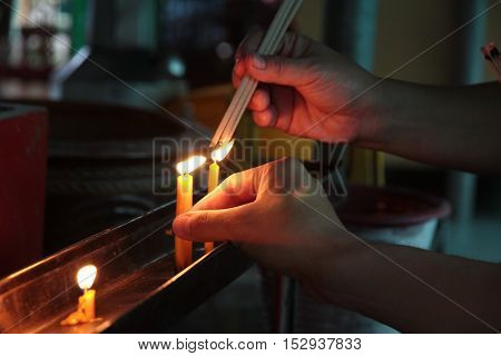 Buddhists make merit,Placing a lighted candle and lit incense with candles frame on the altar of Buddha  at temple.  Selective focus.