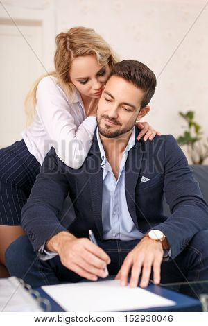 Blonde gold digger woman close to rich boss in office while signing contract