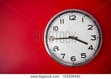 close up modern big clock on red wall