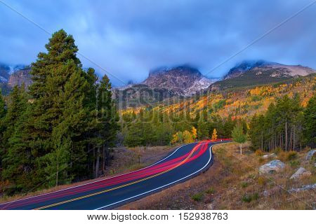 Car Trails Going up Bear Lake road in Rocky Mountain National Park right before sunrise on a cloudy stormy autumn morning