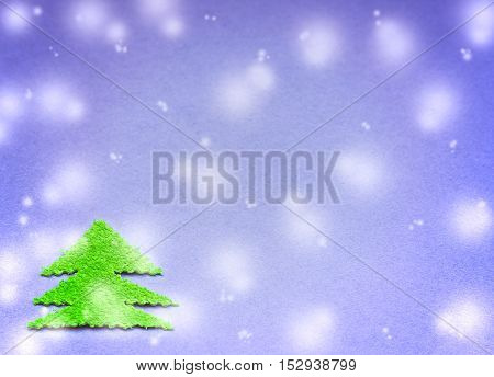 green Christmas tree cut from plush material on the surface of the blue paper and falling snow