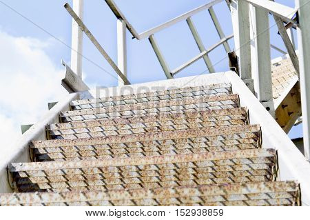 pictured stage metal ladder on a background of blue sky