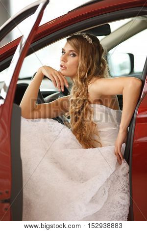 Young sensual bride sits in the red car.Selective focus.Professional hair and make -up
