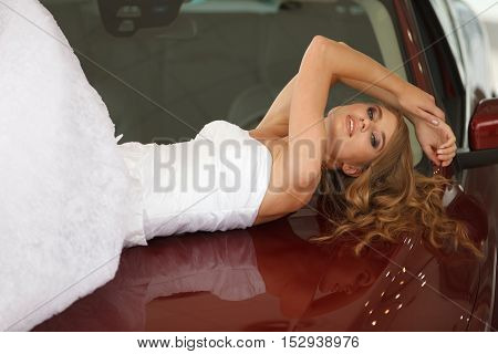 Young sensual bride lies on the red car bonnet and shows emotions