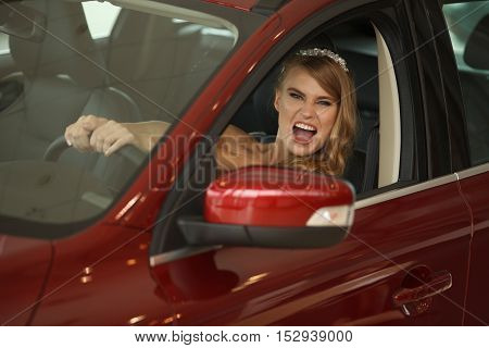 Young sensual bride sits in the red car and shows emotions .Selective focus. Focus on the background