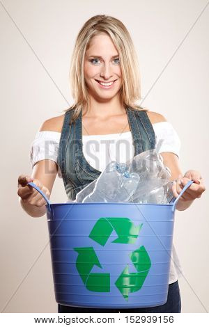 Woman holding a recycling bin filled with plastic.Studio shoot