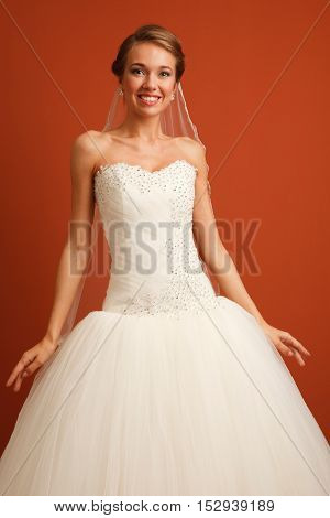 Young classical cheerful bride on the bright brown background