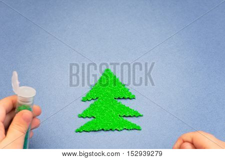 a children's hands sprinkled with glitter Christmas tree cut out of plush on blue paper background