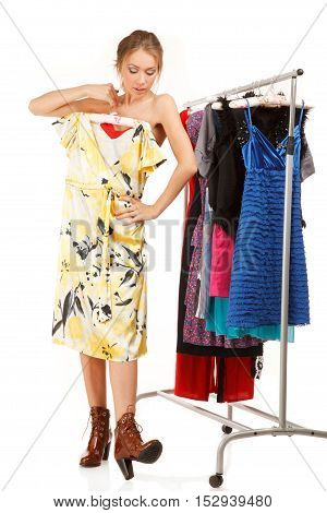 Woman is choosing dresses . She stands near her clothes rack with lots of dresses