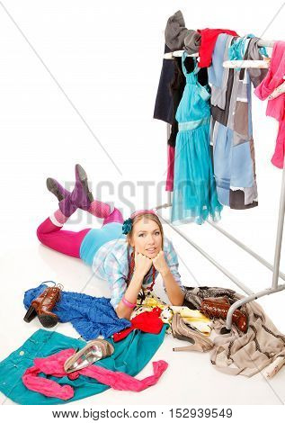 Young woman lies near her clothes rack with lots of dressesand some clothes is on the floor
