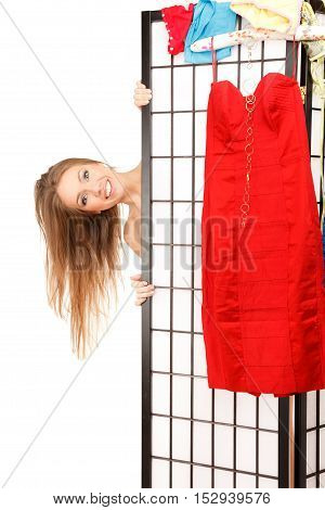 Young beautiful woman looks out of the folding screen red dress is hanging on it