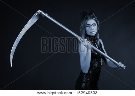 Beautiful woman with a scythe low key portrait