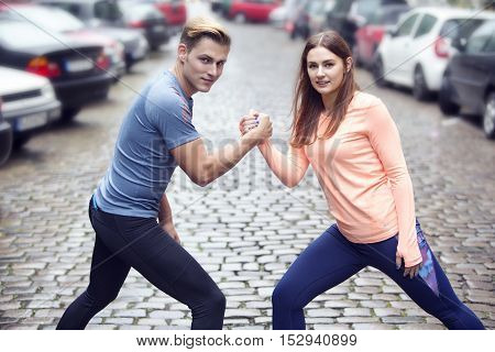 young handsome couple doing workout outdoors in the street