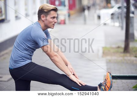 young handsome man stretching outdoors on the pavement