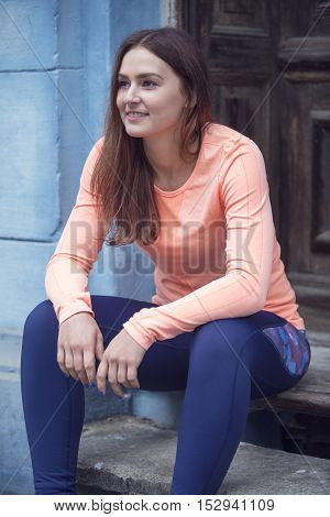 portrait of young brunette sporty woman sitting on stairs at a wooden door