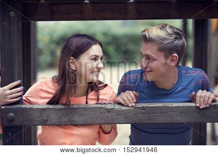 portrait of young sporty couple smiling at each other outdoors