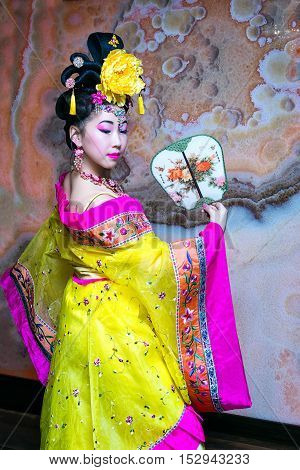 beautiful chinese woman standing in a half-turn in the yellow Chinese national traditional dress with fan