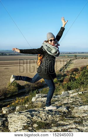 Young joyful woman posing in autumn outfit. Natural outdoors scene. Beauty and fashion. Vertical composition.