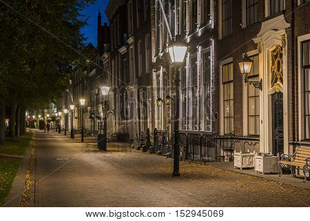 Zierikzee The Netherlands - October 5 2016: Houses at night at the Havenplein in Zierikzee in Zeeland with people The Netherlands.