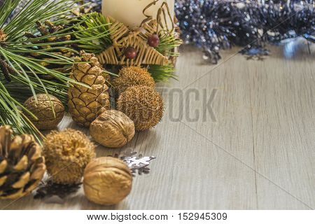 Pine cones with walnuts and candle with christmas decoration on wooden table. Copyspace background.