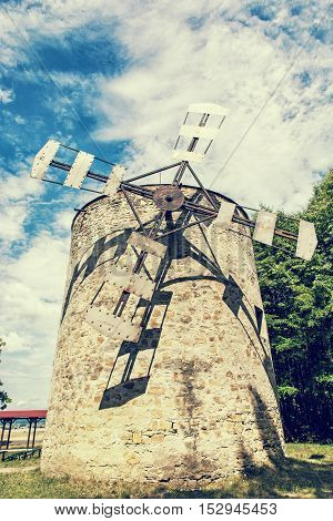 Old tower windmill in Holic Slovak republic. Architectural theme. Vertical composition. Cultural heritage. Retro photo filter. Travel destination.